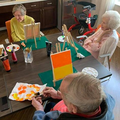 Three seniors painting small canvases during an art class at Heartis.