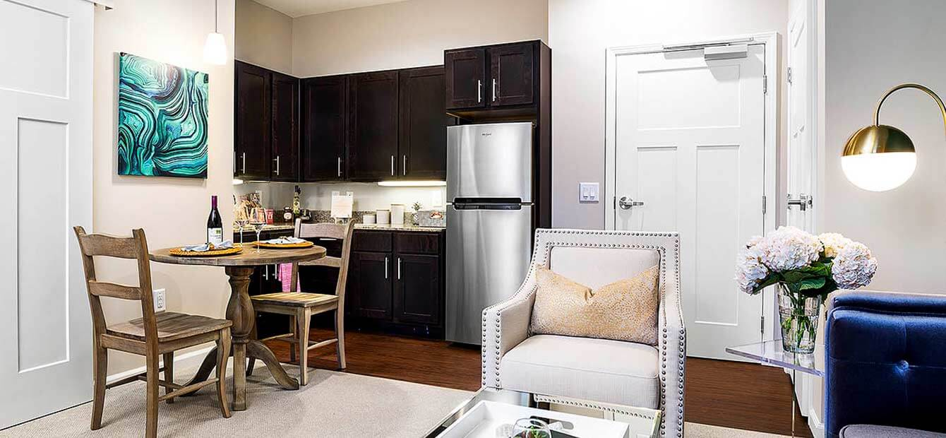 Image displays interior of a Heartis suite. Kitchenette is in the background with cabinets and stainless steel refrigerator. A small dining area is in front of the kitchenette. A sliding barn door opening onto another room is at the left side of the image. On the right of the image is large tufted arm chair.