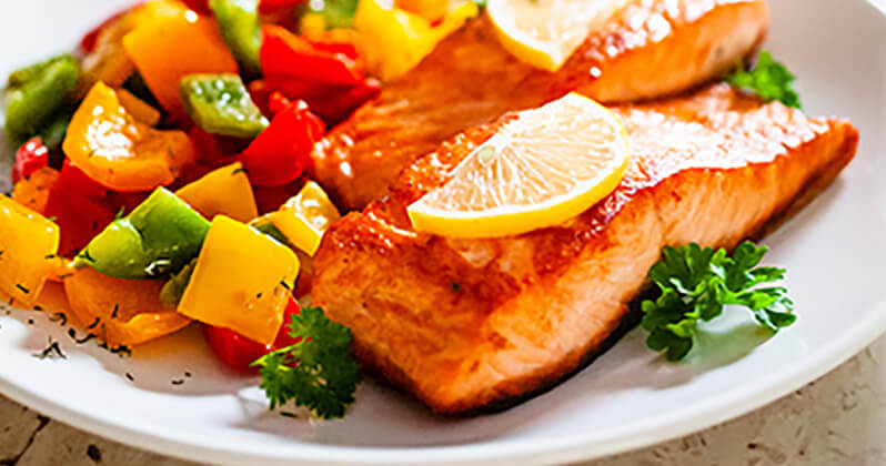 A dish of salmon with lemon slices on top and mixed vegetables.