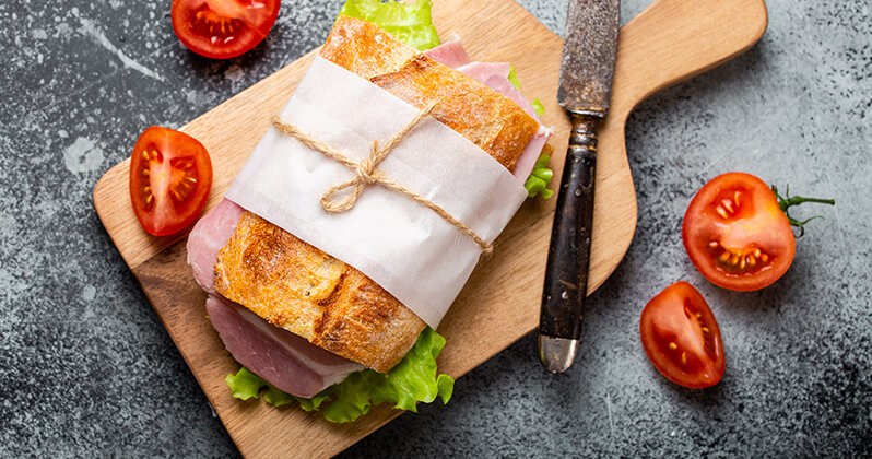 A cutting board with a large sandwich wrapped up in butcher paper. Several cut tomatoes surround the sandwich.