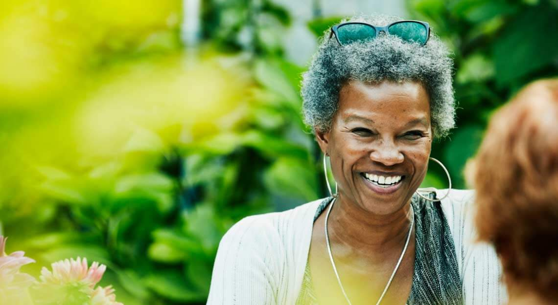 Smiling African American woman with large leafy trees in the background.