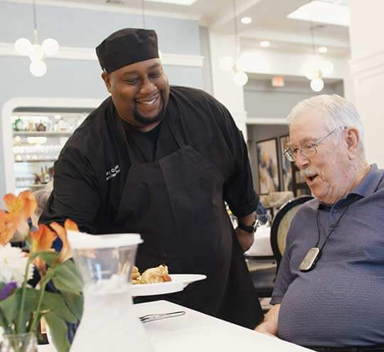 Chef at Heartis location presents a resident with a special meal while the resident looks on appreciatively.