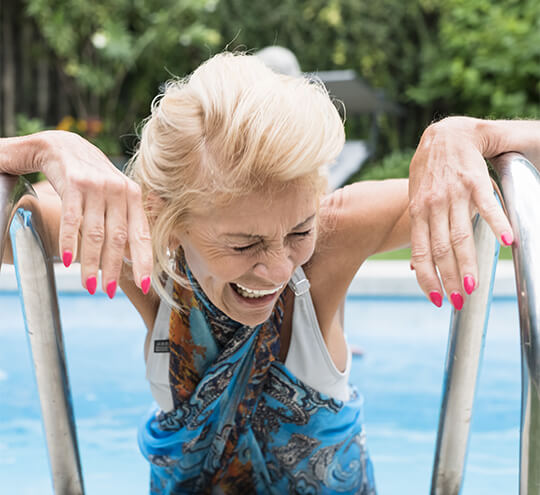 Senior laughing as she steps out of the swimming pool