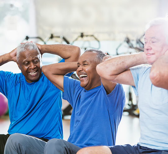 Three senior men in fitness room working out and laughing