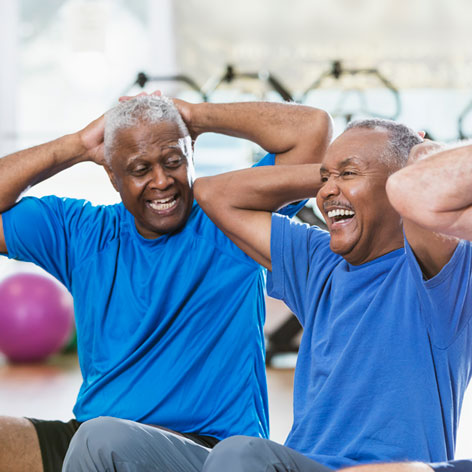 Two Senior men wearing blue t-shirts laughing together while doing a sit up