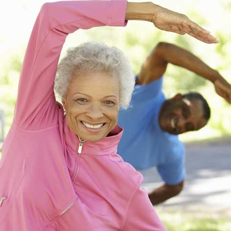 Bucks County Senior man and woman with one arm over their heads doing and excercise