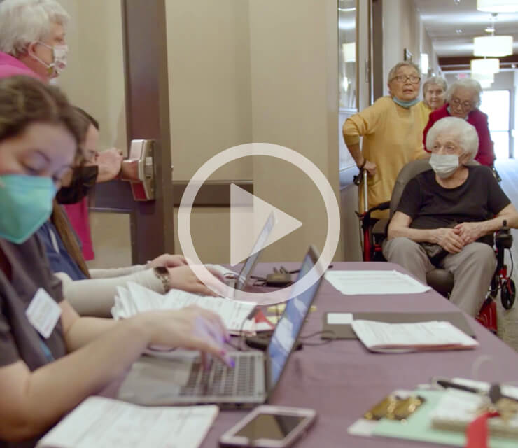 Seniors waiting in line at vaccine clinic while nurses sit at tables with laptops