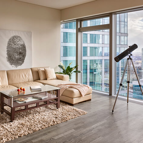 Furnished apartment with floor to ceiling windows, wood floors, sofa with chaise, coffee table and telescope